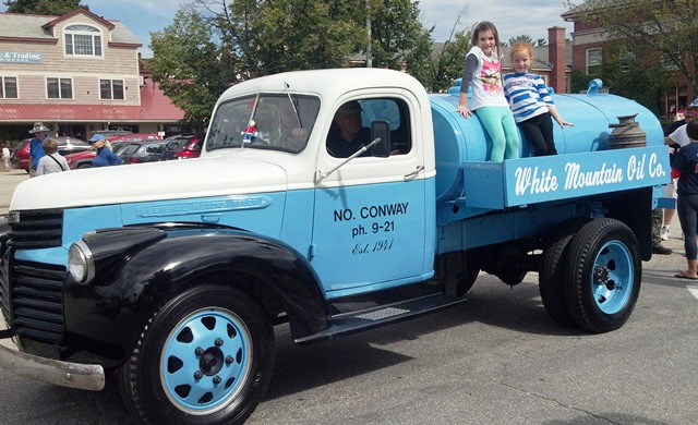 Girls on old oil truck at the mud bowl parade