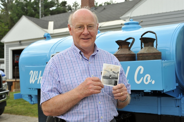 Glenn Saunders  holding a picture of himself on an oil truck at the age of 3 years old